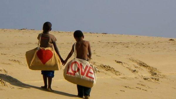 2 jongens op het strand hand in hand met tas van het fairtrade merk Ali Lamu uit Kenia