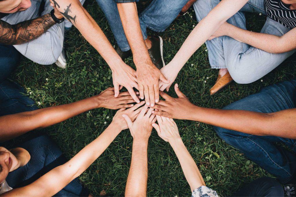 dag van de vrijwilliger 8 armen die elkaar in het midden raken
