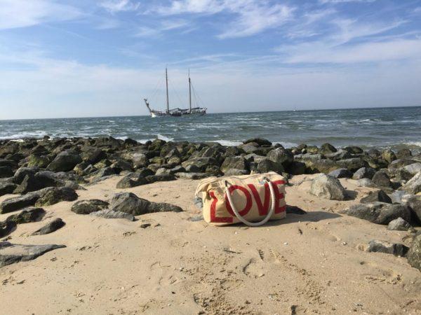 love tas van fairtrade tassen merk Ali Lamu op de achtergrond een stoer schip varend op de noordzee bij terschelling