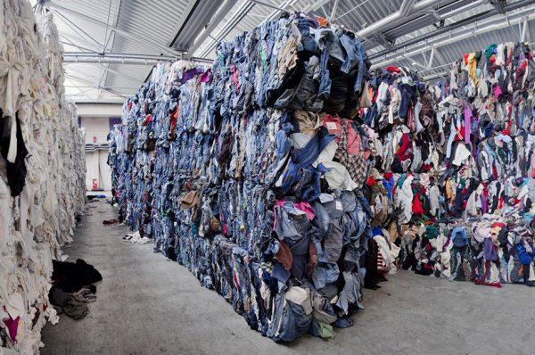 enorme stapels oude kleding die gerecyclede gaan worden tot duurzame producten