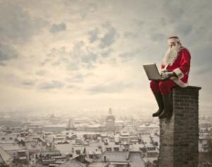 kerstman mannenkerstpakketten zittend op schoorsteen met laptop