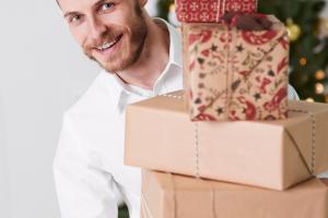 kerstpakketten voor mannen man met stapel cadeaus