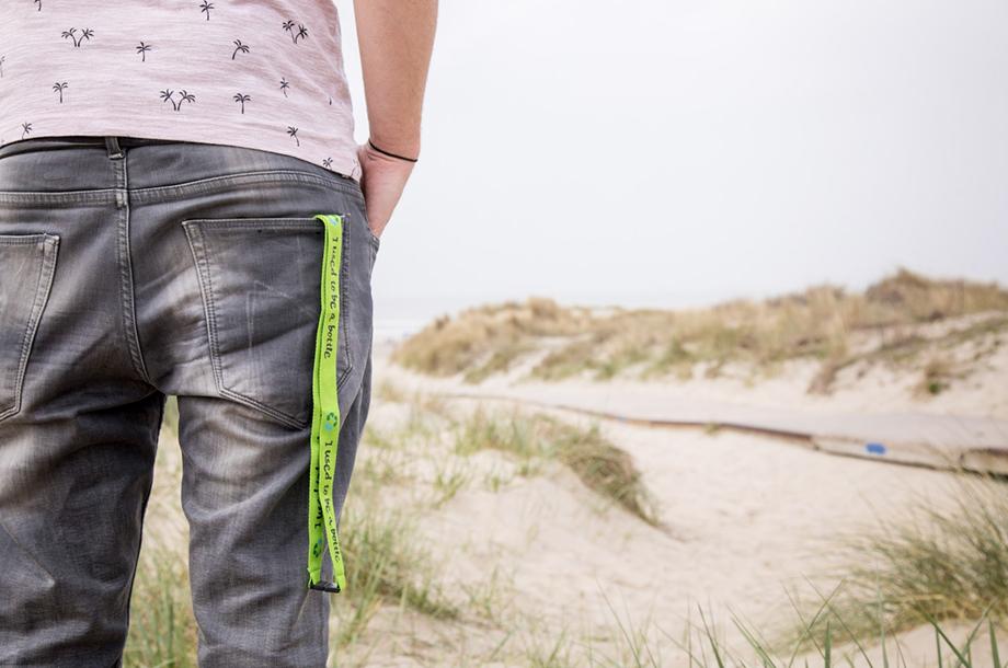 man in de duinen met rpet keycord in broekzak