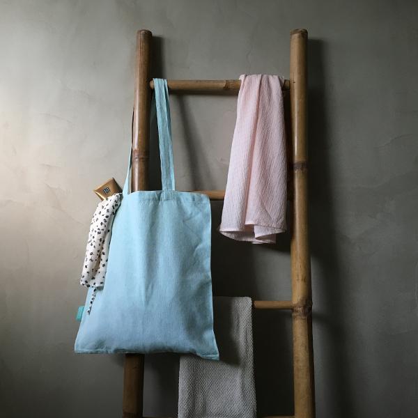 katoenen fairtrade tassen hangend aan trap in de kleuren lichtgrijs, groen en naturel