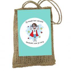 Jute zakje met daarin bloembolletjes. Op het zakje een kaartje met tekst; bedankt voor je zorg. Duurzaam relatiegeschenk.