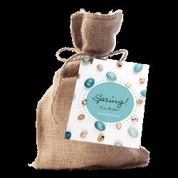 Paas cadeau, een jute zakje met daarin bloembolletjes. Er zit een kaart op het zakje met de afbeelding van paaseitjes