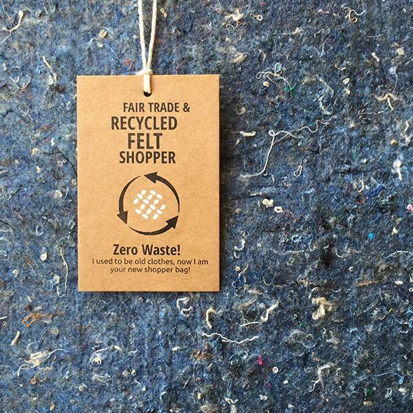 Het kaartje van een fairtrade jeanstas met opdruk zero waste en recycled
